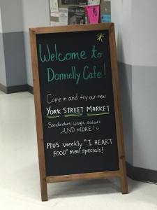 Outside the Donnelly Cafe, a sandwich board advertises the York Street Market. Photo by Sarah Gabrielli